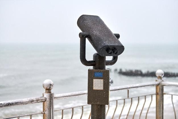 Verrekijker met muntinworp naast de promenade aan het water