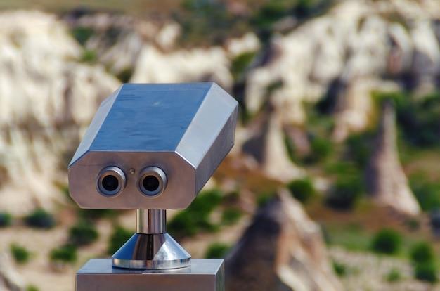 Verrekijker met natuurlijke vulkanische rotsformaties panoramisch uitzicht op de achtergrond. devrent valley cappadocia, turkije. - afbeelding
