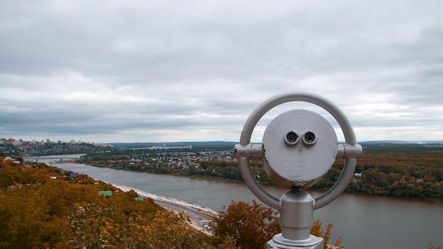 Verrekijker op het observatiedek. uitzicht op de bergen van de stad en het herfstbos.