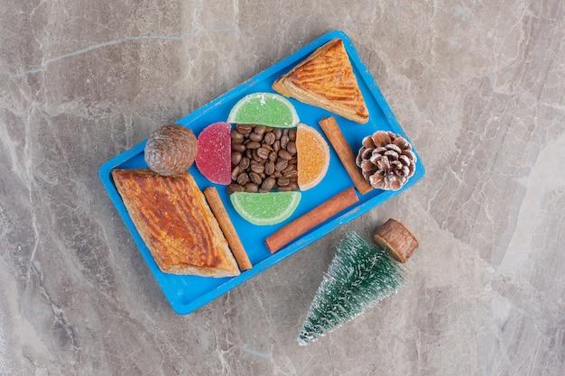 Verrukkelijk arrangement van jam, koffiebonen, kyata's, kaneelstokjes, dennenappels en een boomfiguur op marmer.