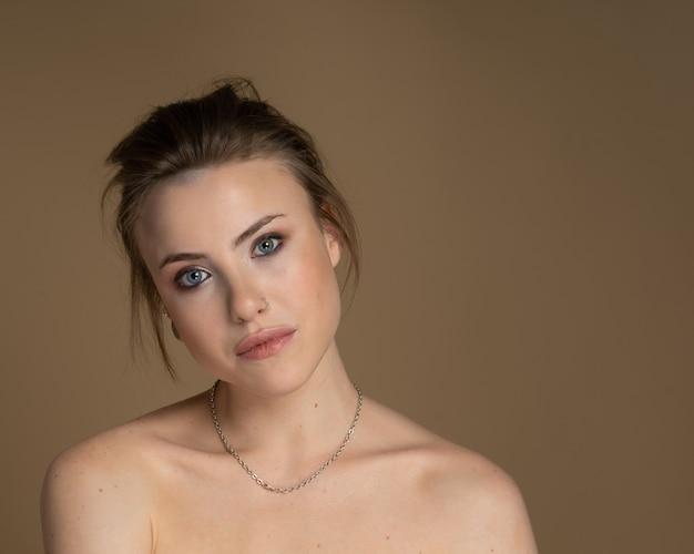 Verrukkelijk meisje met heterochromie, neuspiercing en plug in één oor, en vreemd kapsel. met geweldige professionele make-up en zilveren ketting om haar nek. beige achtergrond. studio opname