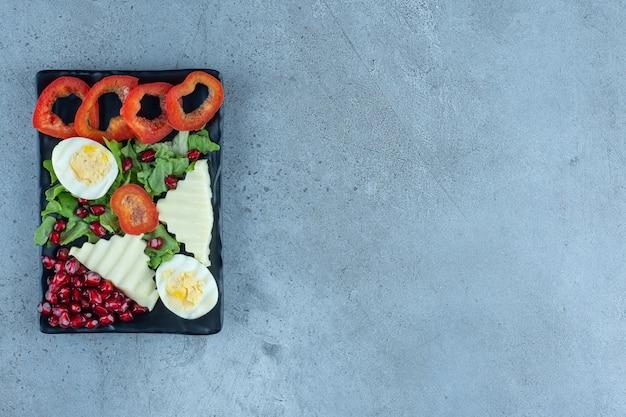 Verrukkelijk, uitgebreid ontbijt op een zwarte schaal op marmer.