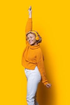 Verrukkelijk zwart-wit portret van een blanke vrouw met blond haar, luisteren naar muziek met een koptelefoon op een gele muur