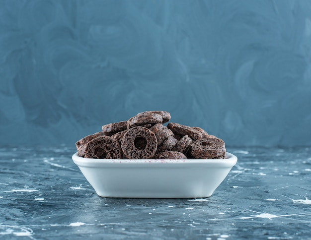 Verrukkelijke chocolade gecoate maïsring in een kom, op de marmeren tafel.