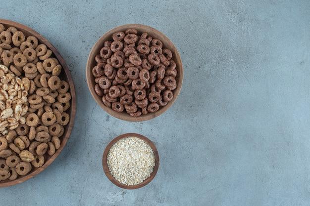 Verrukkelijke cornflakes in de houten kommen, op de blauwe achtergrond. hoge kwaliteit foto