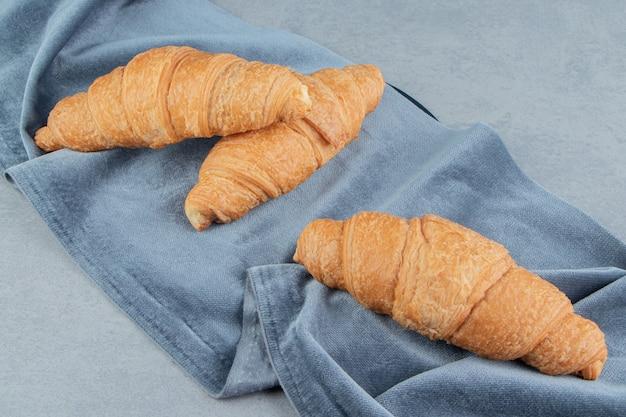 Verrukkelijke croissant op handdoek, op de marmeren achtergrond. hoge kwaliteit foto