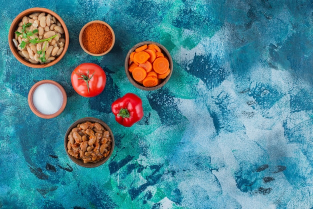 Verrukkelijke gebakken bonen in kommen met groenten, op de blauwe tafel.
