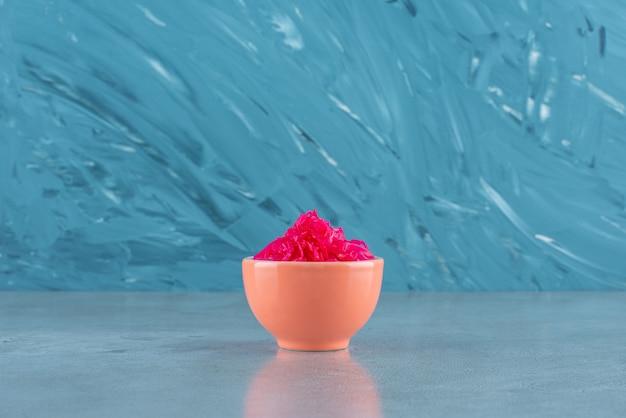 Verrukkelijke gefermenteerde rode kool ligt in een kom, op de blauwe tafel.