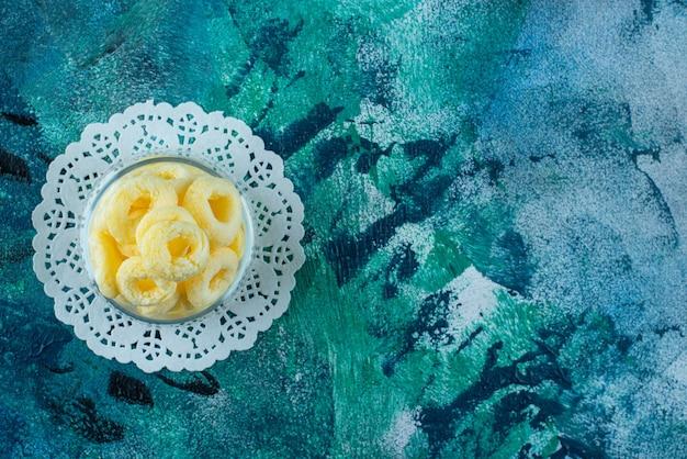 Verrukkelijke maïsringen in een kom op onderzetter, op de blauwe tafel.