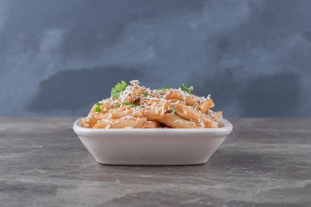 Verrukkelijke penne pasta in de kom, op het marmeren oppervlak.