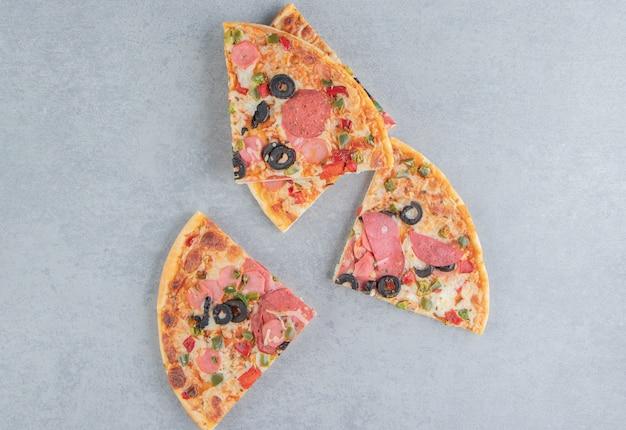 Verrukkelijke plakjes pizza gebundeld op marmer