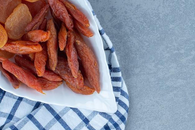 Verrukkelijke twee soorten gedroogd fruit, in kom, op de handdoek, op de marmeren tafel.
