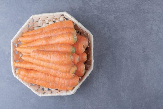 Verrukkelijke wortelen in de kom, op het marmeren oppervlak.