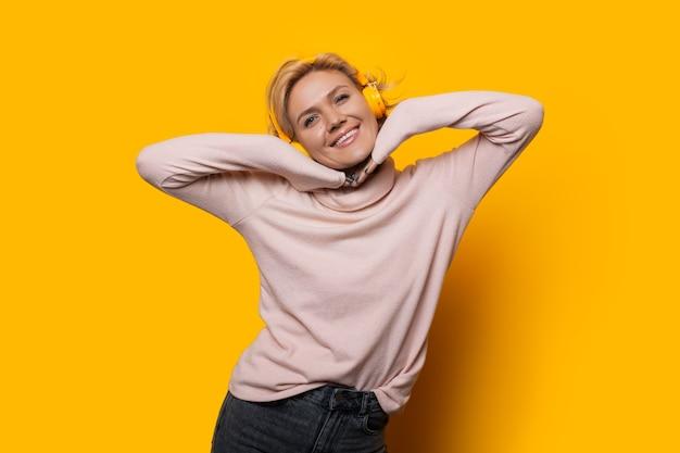 Verrukking kaukasisch meisje met blond haar is gelukkig poseren op een gele achtergrond terwijl ze naar muziek luistert