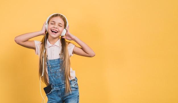 Verrukkingsmeisje die luisterend de muziek op hoofdtelefoon tegen gele achtergrond genieten