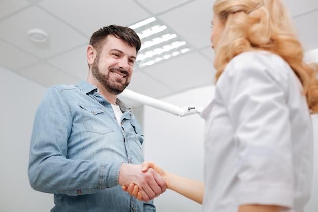 Verrukte arts en haar gelukkige patiënt die een arts de hand schudden en zijn dankbaarheid betuigen na het ondergaan van enkele tandheelkundige ingrepen