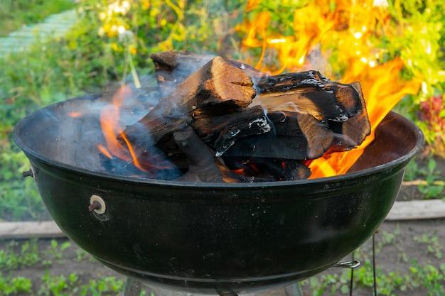 Vers aangestoken barbecuevuur met houtblokken over kleine stukjes aanmaakhout in een draagbare bbq