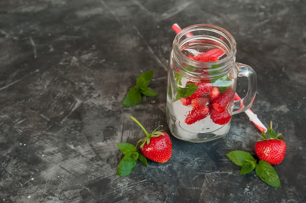 Vers aardbeienclose-up terwijl in een cocktailkruik. rijpe aardbeien in een zomer verfrissende cocktail op een donkere achtergrond en kopie ruimte.