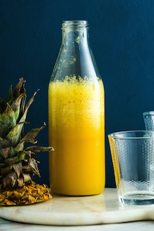 Vers ananassap op een lijst in een fles en glazen