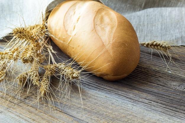 Vers baguettes gebakken brood en tarwearen op houten achtergrond