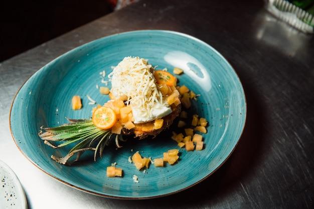 Vers bereide salade ligt in de ananas, die in de lengte wordt gesneden en bestrooid met geraspte kaas. alles ziet er erg smakelijk uit.