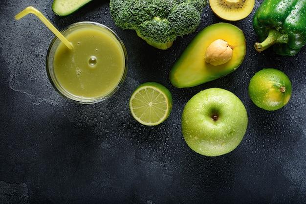 Vers bereide smoothie en ingrediënten groene groenten en fruit liggen op een natte stenen ondergrond