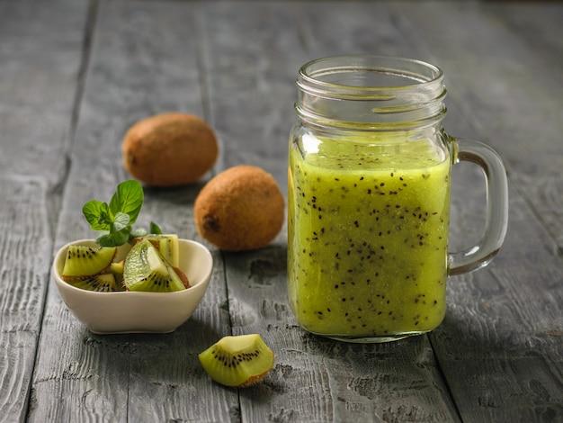 Vers bereide smoothie van plakjes kiwi, appel, munt en kiwi op de zwarte rustieke tafel