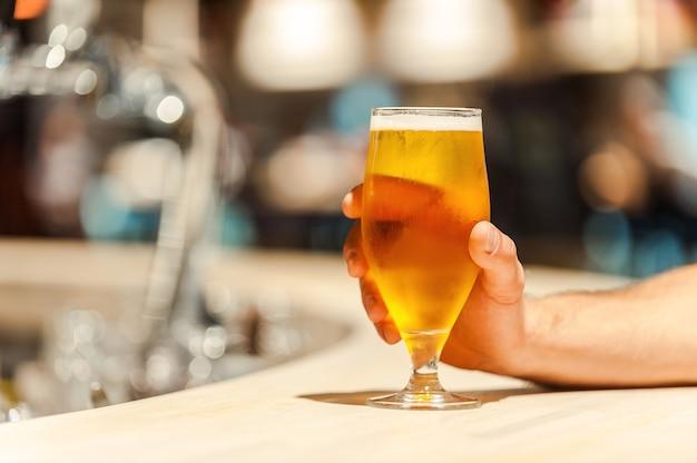 Vers bier. close-up van een man die de hand op een glas bier houdt terwijl hij aan de bar zit