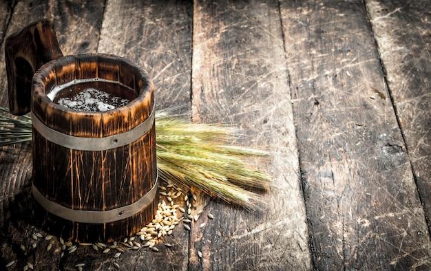 Vers bier in een houten mok op houten tafel.