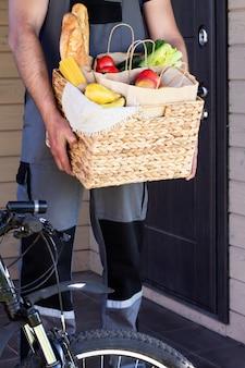 Vers biologisch brood, groenten, groenten en fruit, granen en pasta in een rieten mand in de handen van een fietskoerier. fiets milieuvriendelijke levering of schenking van ecologisch boerderijvoedselconcept.