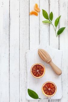 Vers bloed oranje vruchten met houten juicer op witte houten achtergrond