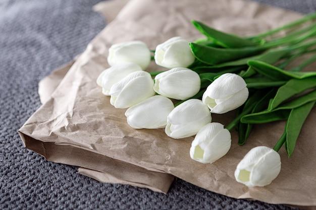 Vers boeket van witte tulpen over gerecycled papier op een grijze achtergrond