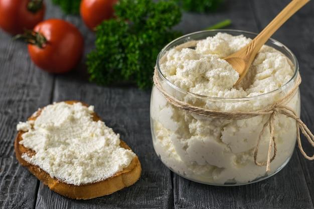 Vers brood besmeurd met verse kwark op een houten tafel. het concept van gezonde voeding.