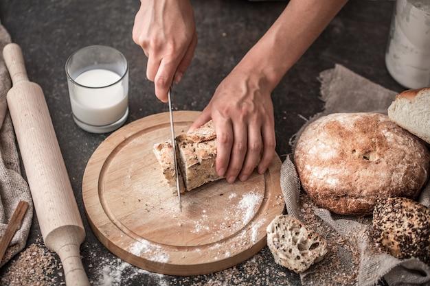 Vers brood in handen close-up op oude houten tafel