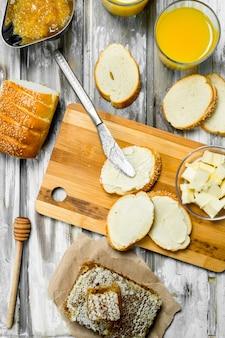 Vers brood met boter en sinaasappelsap. op houten rustieke ondergrond