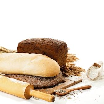 Vers brood op snijplank, schep met bloem en zaden geïsoleerd dan wit