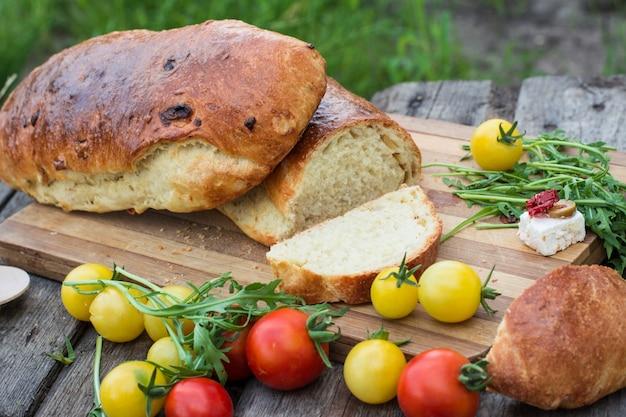 Vers brood. tomaten met rucola. feta-kaas met olijven en in de zon gedroogde tomaten. picknick,