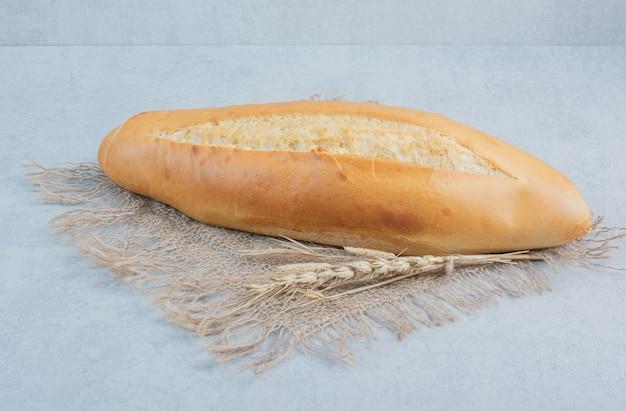 Vers broodbrood op jute met tarwe. hoge kwaliteit foto
