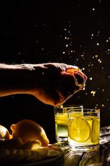 Vers citroensap. focus op het nabije glas en de hand