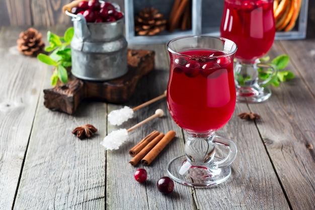 Vers cranberrysap met kaneel en anijs in glazen potten op het oude houten oppervlak. selectieve aandacht.
