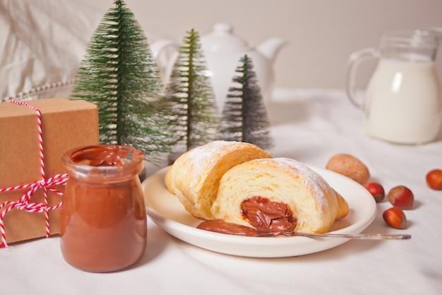 Vers croissantsbroodje met chocolade, kop van koffie, pot melk in de buurt, drie kleine kerstboom speelgoed en geschenkdoos op wit