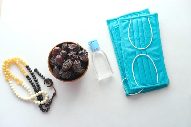 Vers datumfruit in een kom gebed rozenkrans handdesinfecterend middel en masker op de vloer