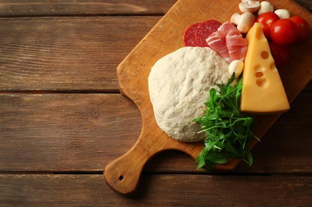 Vers deeg en andere verschillende ingrediënten voor pizza op houten achtergrond