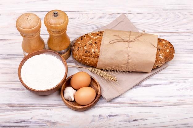 Vers deeg over witte lijst met bloem. home brood bakken oppervlak. proces om eigengemaakt brood te maken. deeg voorbereiden om te bakken. biologische ingrediënten voor broodbereiding. plat leggen, ruimte voor tekst