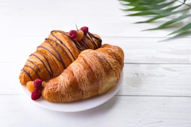 Vers die croissant met bessen en palmverlof op witte houten achtergrond wordt geïsoleerd
