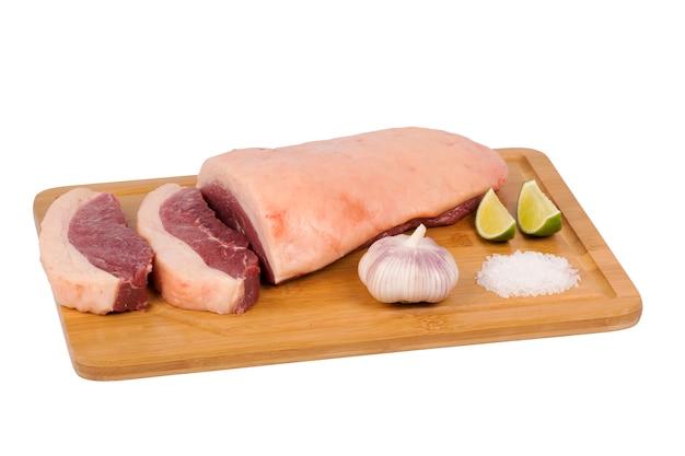 Vers en rauw rundvleesvlees op snijplank op witte achtergrond.