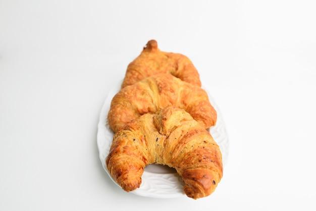 Vers en smakelijk croissant in witte plaat witte lijst.