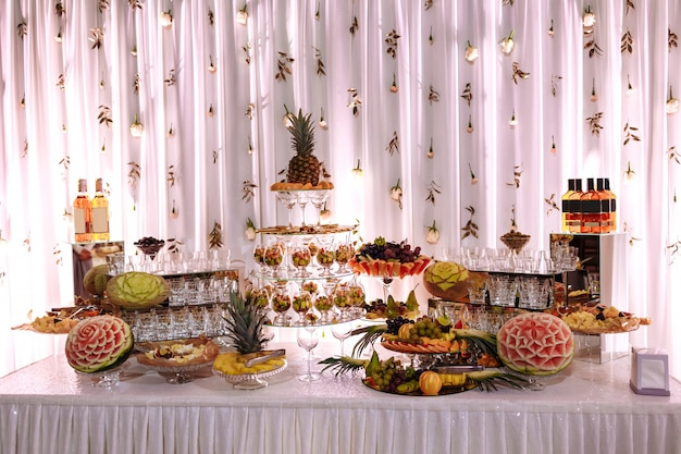 Vers, exotisch, biologisch fruit, lichte snacks in een bord op een buffettafel. geassorteerde mini-delicatessen en snacks, restauranteten op evenement. versierde heerlijke tafel voor feestartikelen.