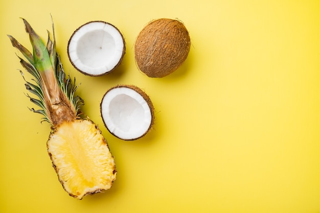 Vers fruit, ananas en kokosnoot, op gele getextureerde zomerachtergrond, bovenaanzicht plat, met kopieerruimte voor tekst