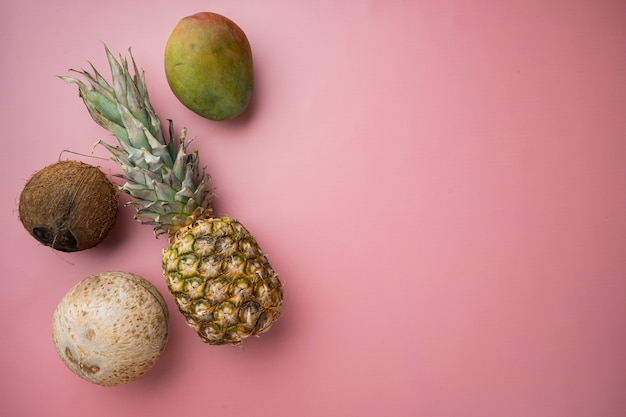 Vers fruit, ananas en kokosnoot, op roze getextureerde zomerachtergrond, bovenaanzicht plat, met kopieerruimte voor tekst